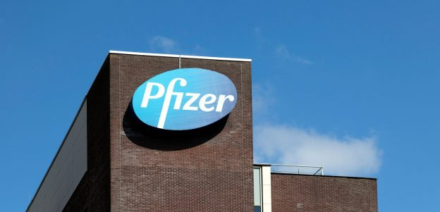 "Close up shot of the ""Pfizer"" office building with the logo on the side, against a blue sky with white clouds."