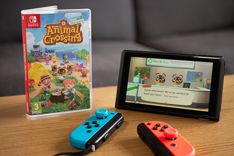 United Kingdom -- March 2020: Nintendo Switch with Joy Con controllers and Animal Crossing: New Horizons. (By Vantage_DS)
