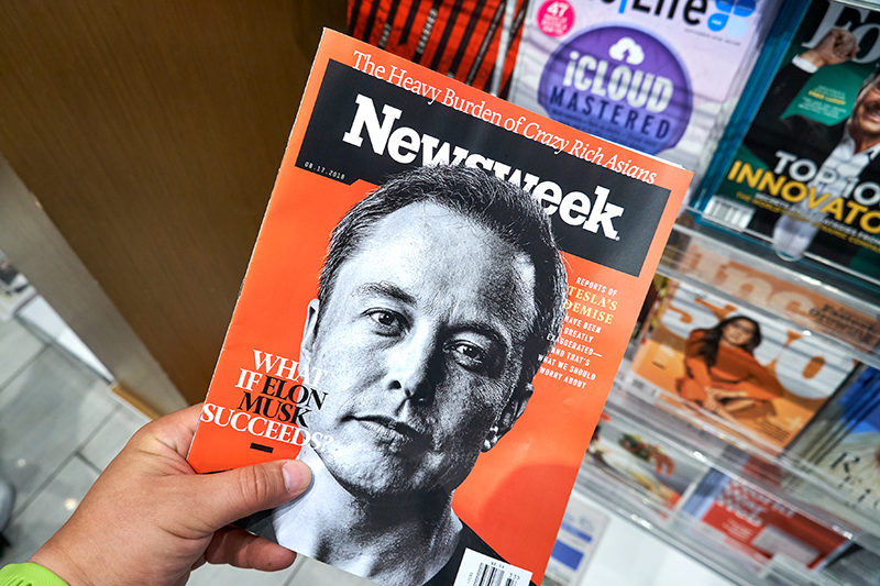 Newsweek magazine with Elon Musk on main page in a hand.